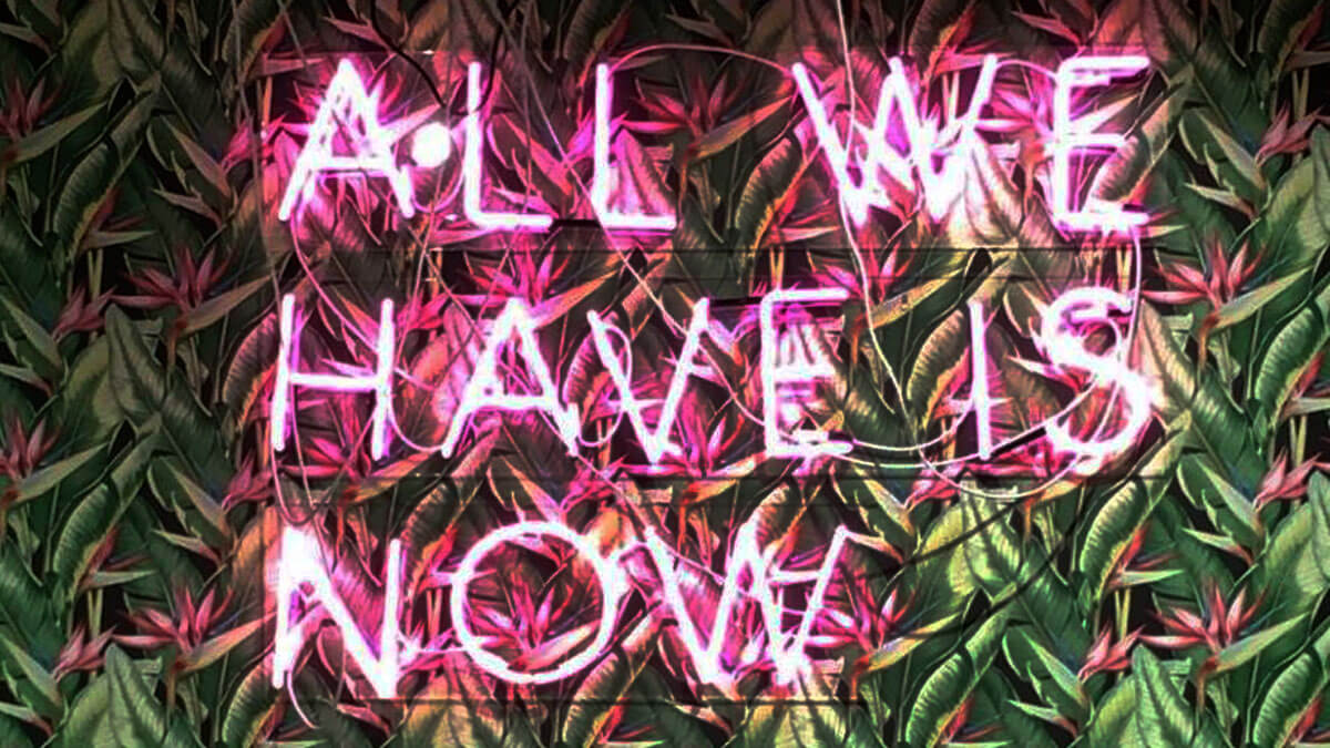 "De tekst ""All we have is now"" prijkt in neon op de muur bij NOW Fashion"